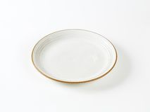 White plate with brown rim Royalty Free Stock Image