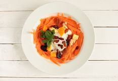 White plate with carrot salad with dried fruits and jogurt. Carrot salad with dry fruits and natural yogurt royalty free stock photography