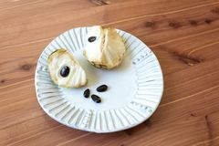 White plate centered with two sections of a ripe cherimoya fruit Annona cherimola  with large black seeds exposed. Wood background, horizontal aspect Royalty Free Stock Photo