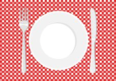 White plate on a checkered tablecloth.  Stock Images