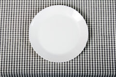 White plate on checkered tablecloth - kitchen background Royalty Free Stock Photo