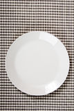 White plate on checkered tablecloth - kitchen background Royalty Free Stock Images