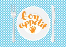 White plate on a checkered tablecloth. Lettering - Bon appetit.  Stock Photos
