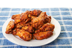 White Plate of Chicken Wings on Blue Mat Royalty Free Stock Image