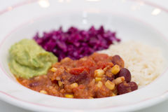 White plate of chili sin carne with red cabbage, guacamole and r. Ice on white background Royalty Free Stock Image