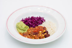 White plate of chili sin carne with red cabbage, guacamole and r. Ice on white background Stock Photography
