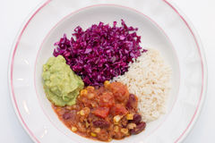 White plate of chili sin carne with red cabbage, guacamole and r. Ice on white background Royalty Free Stock Photo