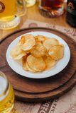 White plate with chips on a round wooden board. White plate with chips on a circular wooden board on the background glasses with beer Stock Image