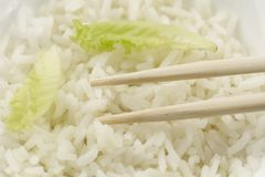 White plate of cooked long-grain rice on wooden background. Healthy eating, diet Royalty Free Stock Photos
