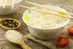 White plate of cooked long-grain rice on wooden background. Healthy eating, diet Stock Images