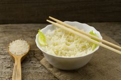 White plate of cooked long-grain rice on wooden background. Healthy eating, diet Royalty Free Stock Photo