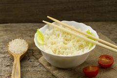 White plate of cooked long-grain rice on wooden background. Healthy eating Royalty Free Stock Images