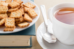 White plate with crackers on an old book Royalty Free Stock Photography