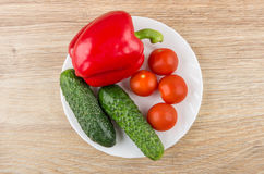 White plate with cucumbers, sweet pepper and tomatoes cherry. On wooden table. Top view Stock Photography