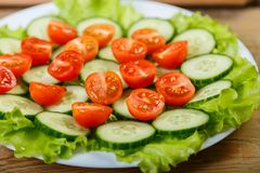 On a white plate are cucumbers, tomatoes and lettuce leaves. Front view, close-up Stock Photo