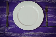 White plate with cutlery on a lilac wooden surface. The view from the top Stock Images