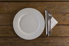 White plate with cutlery and napkin on table Stock Images