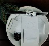 White plate with cutlery and sheets of paper on a wooden background. inscription - happy new year. space for text. top Royalty Free Stock Photos