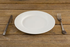 White plate with cutlery on table. Close-up of white plate with cutlery on table Royalty Free Stock Photography