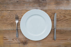 White plate and cutlery on wood Royalty Free Stock Photo
