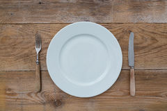 White plate and cutlery on wood Stock Photos