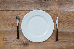 White plate and cutlery on wood Stock Image