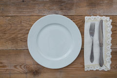 White plate and cutlery on wood Royalty Free Stock Images