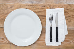 White plate and cutlery on wood Stock Photography