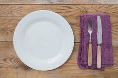 White plate and cutlery on wood Stock Photo