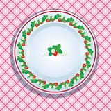 White plate decoration with strawberries, leaves and flowers on. Pink checkered background. Fruit frame Stock Photography
