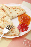White plate with delicious pancakes. Delicious pancakes with red and yellow jam on white plate Stock Image