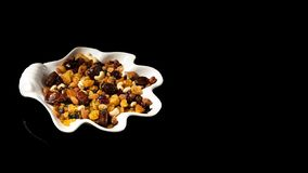 White plate of dried fruits on black background, with reflection. Mix of nuts and berries: raisins, hazelnut, cashews. Almonds, cranberries, dried dates and stock image