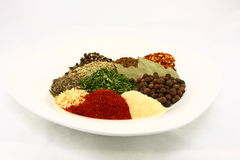 White Plate Filled With Dried Herbs And Spices Stock Images