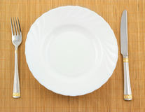 White plate, fork and knife Royalty Free Stock Image