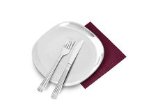 White plate, fork and knife on brown napkin Royalty Free Stock Images