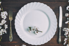 White plate with a fork and knife on a brown wooden surface. View from the top Royalty Free Stock Image