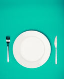 White plate, fork and knife Royalty Free Stock Photography