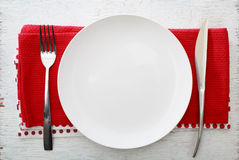 White plate with fork and knife. On red napkins stock photos