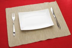 White plate fork and knife on red table Stock Photo