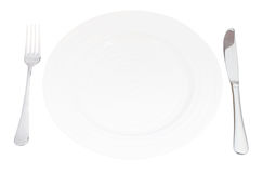 White plate with fork and knife set isolated Stock Images