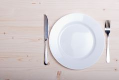 White plate and fork next to a knife on a wooden board top view Stock Images