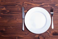 White plate and fork next to a knife on a wooden board top view Royalty Free Stock Images