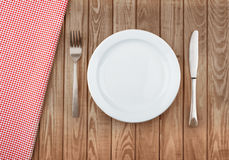 White plate and fork on old wooden Stock Photo