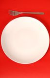 White plate with fork on red background Royalty Free Stock Image