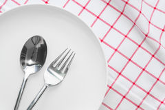 White plate and fork spoon on red checked Royalty Free Stock Image