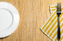 Plate and fork on a napkin on the table stock images