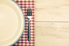 White plate and fork on tablecloth. Top view  white plate and fork on old wooden table with red checked tablecloth Royalty Free Stock Photo