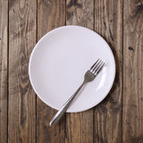 White plate and fork. White plate on a wooden background Royalty Free Stock Image