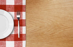 White plate and fork on wooden table Stock Photography