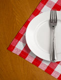 White plate and fork on wooden table w tablecloth. White plate and fork on wooden table with red checked tablecloth Royalty Free Stock Images